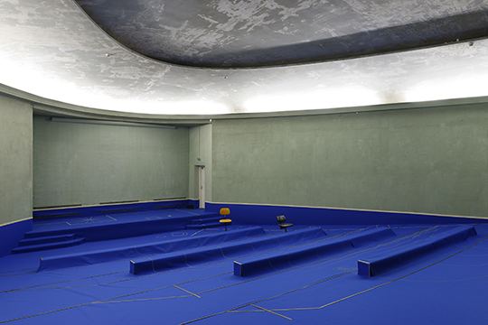 Room with blue carpet and seats, an installation by artist Anne Le Troter titled 'Liste à puces'