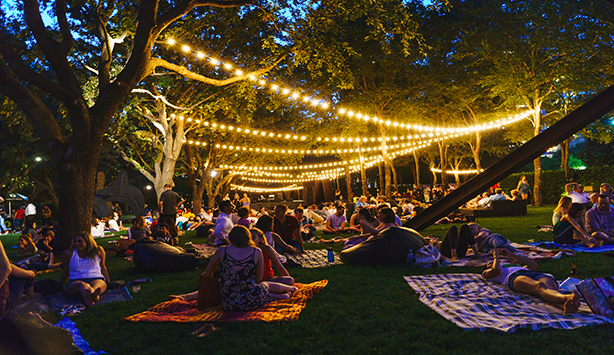 Picture of a crowd of people sitting down on blankets at night under Nasher sculptures and fairy lights