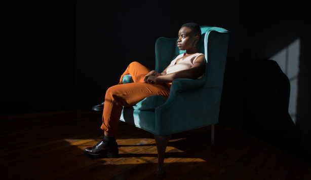 Musician Vagabon sits on a chair in a dark room for a portrait.