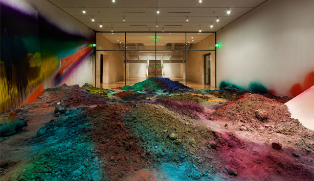 Mounds of brightly spray painted earth cover the gallery floor at Nasher Sculpture Center