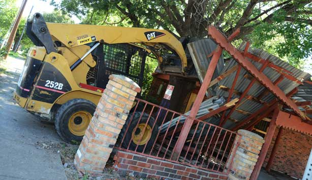 Bulldozer knocks down Oak Cliff house during installation of Lara Almarcegui's artwork, Buried House
